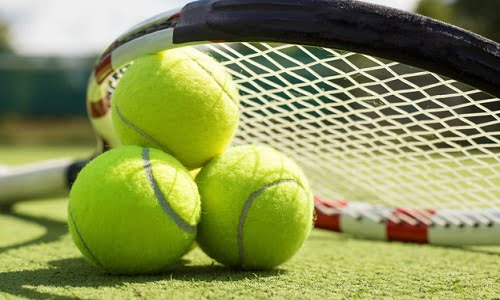 racchetta da tennis con delle vecchie palline, pronte da essere riutilizzate