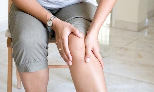 ragazza si tocca il ginocchio poichè soffre di dolori articolari