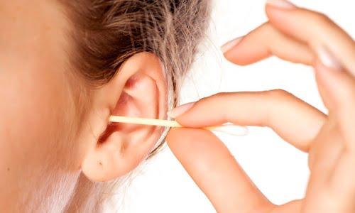 ragazza che soffre di orecchie tappate utilizza un bastoncino di cotton fioc
