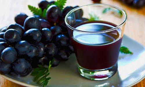 un bicchiere di succo d'uva con il frutto a lato