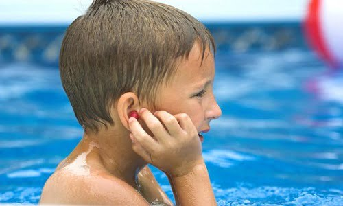 bambino in piscina che soffre per l'acqua nelle orecchie